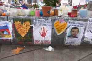 Republique Monument in Paris with posters, notices, lost child, candles and flowers in Paris France