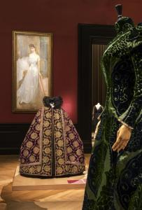 From the exhibit, a Worth housecoat/tea-gown in the foreground, in the center, a modified cape from Tsar Nicolas II and hanging a portrait of Countess Greffulhe© Pierre Antoine
