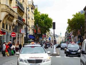 Taxis on rue Saint Antoine in the Marais, Bastille column in background