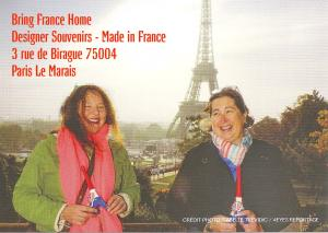 Image of Nathalie and Mathilde Bring France Home Paris Designer Souvenirs Made in France in front of the Eiffel Tower holding their Eiffel Tower souvenir
