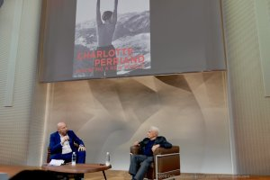 Image of Frank Gehry and Jean-Louis Cohen at the Fondation Louis Vuitton below projected image of Charlotte Perriand exhibition poster