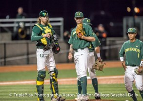 Oregon catcher Matthew Dyer and relief pitcher Cooper Stiles wait with the Duck infielders for another pitcher to enter Thursday's game against Oregon State at PK Park.