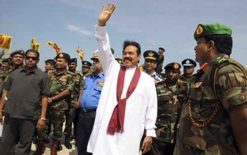 Sri Lankan President Mahinda Rajapaksa waves during a photo opportunity with high-ranking military officials after unveiling a monument for fallen Sri Lankan soldiers in the town of Puthukkudiriruppu