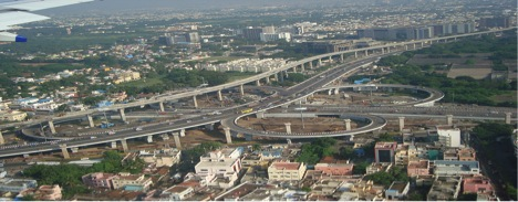 Kathipara Flyover on a National Highway. The Chennai Metro viaduct crosses it and goes above the clover leaf. Both road and rail provide intermodal connectivity to the Airport