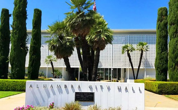 5 palm trees in front of Alhambra City Hall with lettering on the wall spelling is name.