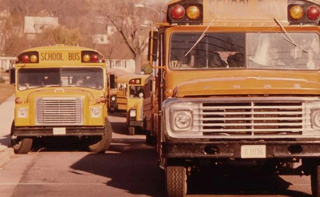Students arriving by school bus in early 70s (Photo - The U.S. National Archives).