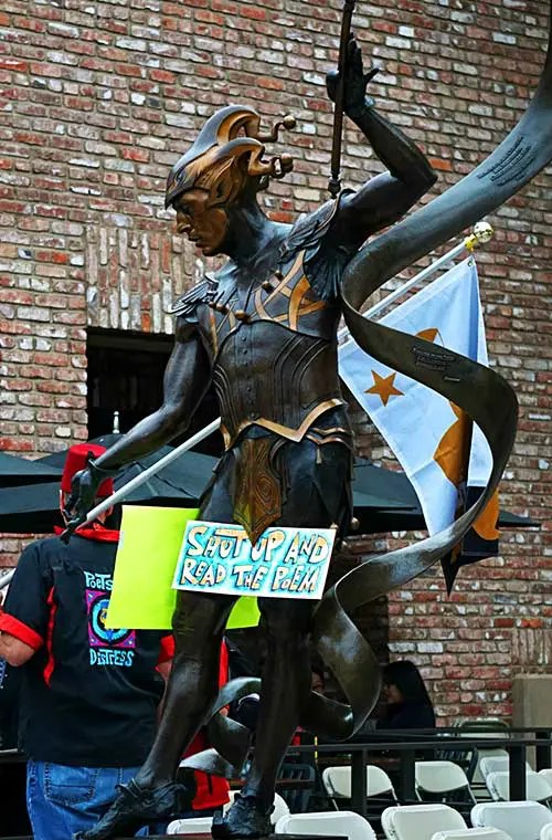 A bronze statue with a sign that hiding its crotch