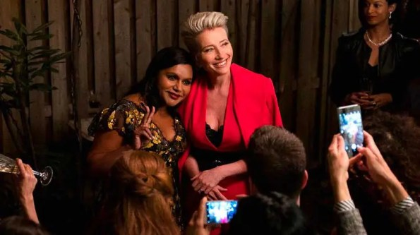 a lasy in a red blazer is hugging an indian looking lady in a dark dress in front of the press
