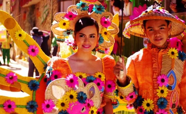 A man and a woman in colorful matching outfits and balloons matching the colors of their clothes