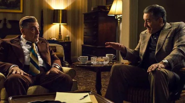 two men in suits talking to each other in a fancy home