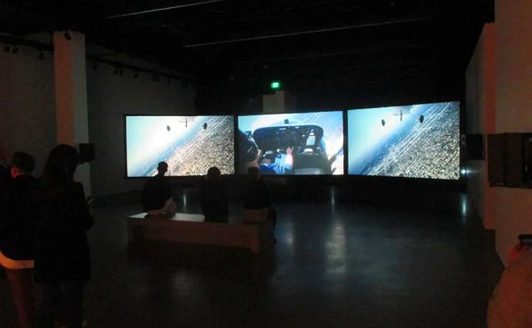 A 3 screen projection in a dark room with people watching it
