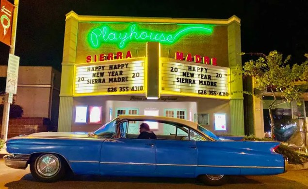 A blue car in front of a theatre