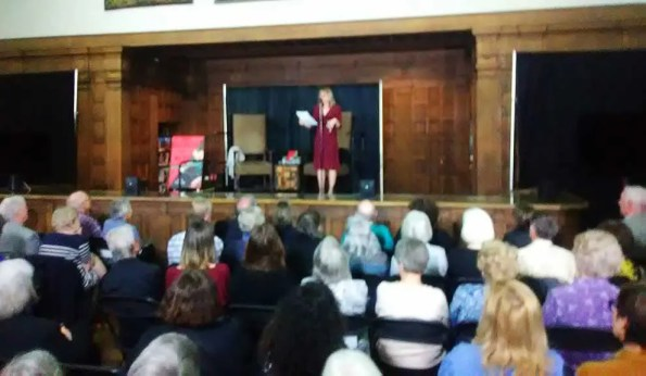 A woman in a burgandy dress speaking to an audience