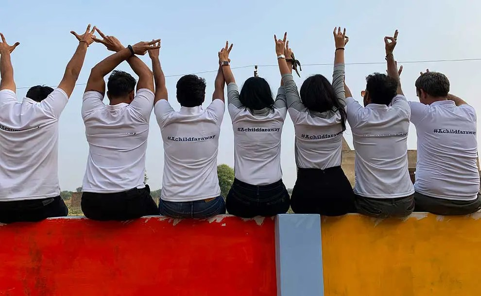 Staff raising their hands sitting on a color painted wall