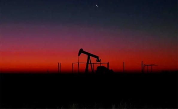 A silhouette of an oil pump in gthe dusk