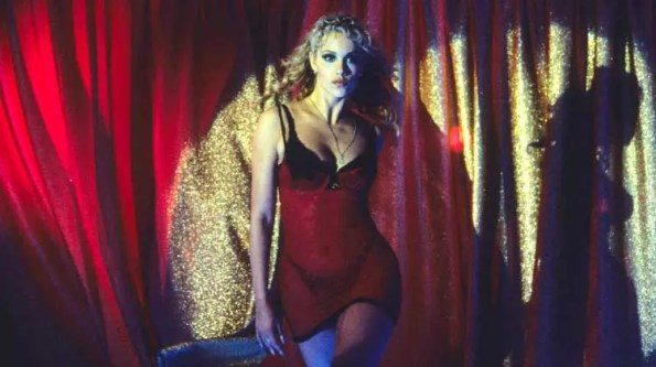 A woman in a red lingerie and black bras in front of a red curtain