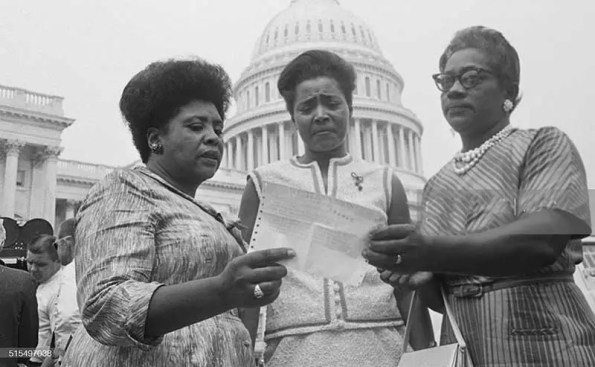 Three black women holding a paper in hand