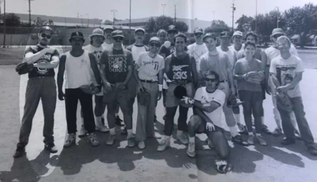 Black and white photo of q group of guys at a softball game