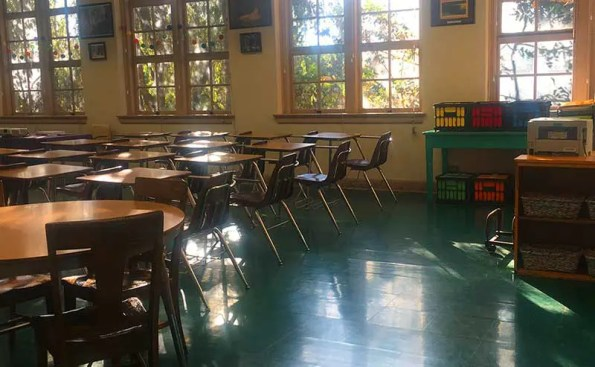 desks in a classroom and sun rays