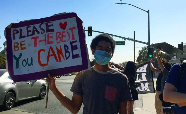 A young black person holding a sign encouring love
