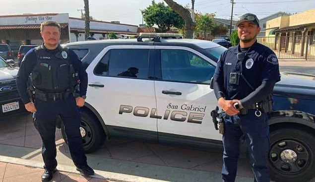 2 police officers standing in front of their cruiser