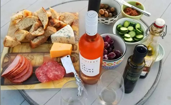 a platter of maza food and a wine bottle