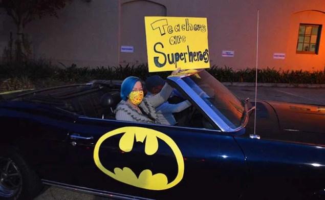 a woman in a car with Batman logo on it