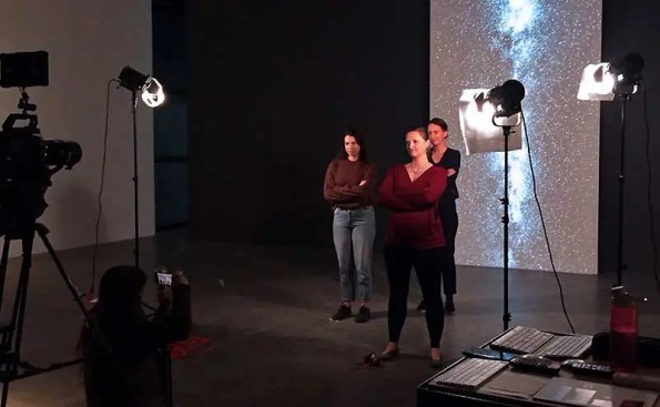 3 women stand in a studio while being filmed