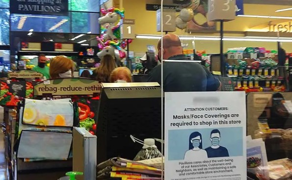 customers at a store and a safety sign on window