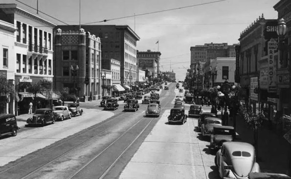 a black and white photo of a street and cars