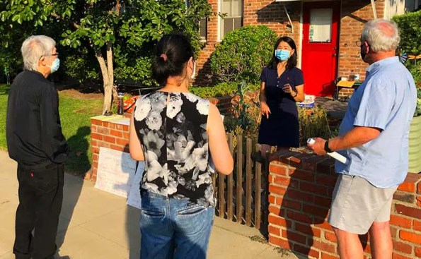 one woman with a mask talking to neighbors