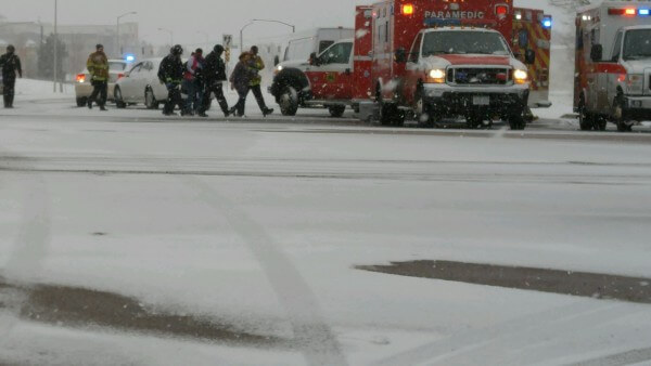 People escort an injured person to an ambulance.