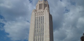 The Nebraska Statehouse towers in front of a cloudy sky.