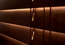 Closed venetian blinds with an orange glow cast outside.