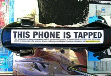 """This Phone is Tapped"" is written on a public phone."
