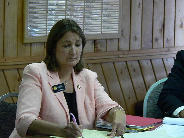 Ellen Roberts sits at a desk.