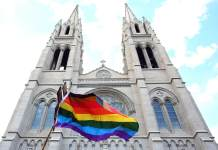 A demonstrator raises a rainbow colored flag while passing the Cathedral Basilica of the Immaculate Conception on Colfax Avenue during the Pride Liberation March in coordination with Black Lives Matter 5280 in Denver, June 14, 2020.