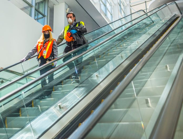 Workers ride the escalator at the Colorado Convention Center, which is being turned into an alternative care site for COVID-19 patients on April 14. (Photo by Evan Semón)