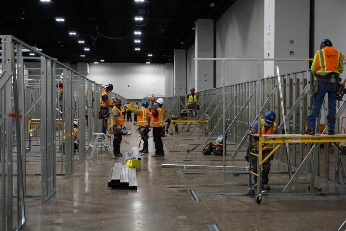 Workers construct the alternative care site for COVID-19 patients at the Colorado Convention Center on April 10, 2020. (Photo by Forest Wilson)