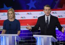 Colorado Sen. Michael Bennet speaks as Sen. Kirsten Gillibrand of New York looks on during the second night of the first Democratic presidential debate on June 27, 2019 in Miami. A field of 20 Democratic presidential candidates was split into two groups of 10 for the first debate of the 2020 election, taking place over two nights at Knight Concert Hall of the Adrienne Arsht Center for the Performing Arts of Miami-Dade County, hosted by NBC News, MSNBC, and Telemundo. (Photo by Drew Angerer/Getty Images)