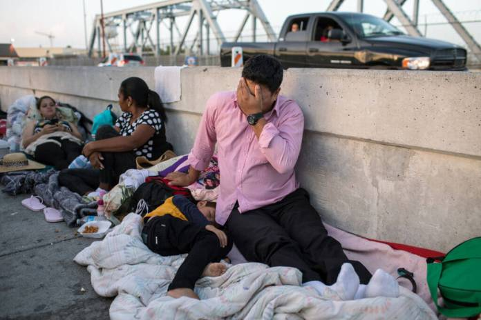 A Honduran man and his 5-year-old son wait on the Mexican side of the Brownsville- Matamoros International Bridge in Mexico after being denied entry into the United States on June 28, 2018. It is near the site where the bodies of a Salvadoran father and his young daughter were found after they drowned trying to cross the Rio Grande River. (Photo by Tamir Kalifa/Getty Images)
