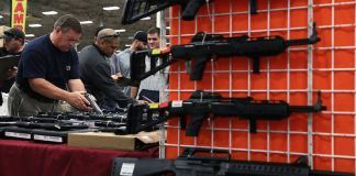 Potential buyers try out guns displayed on an exhibitor's table at an expo in 2016. (Photo by Alex Wong/Getty Images)