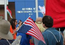 Outside the Aurora ICE Processing Center, an upside down American Flag, which is the signal for distress, is displayed over someones shoulder. (Photo by Cullen Lobe for The Colorado Independent)