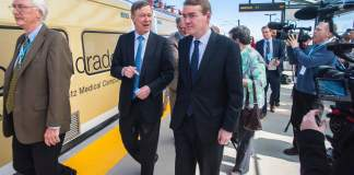 All aboard the 2020 Express: Former Gov. John Hickenlooper, left, and Sen. Michael Bennet — pictured here at the 2016 opening of RTD's A-Line — both want to be president. (Photo by Evan Semón)