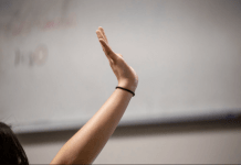 A student at Denver's DCIS Montbello raises her hand during a reading assignment. (Photo by Nathan W. Armes/Chalkbeat Colorado)