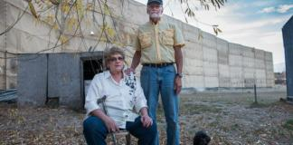 Dawn Stein and Lowell Lewis, neighbors in Triple Creek, pose in front of the newly constructed wall outside of Stein's home. (Ted Wood/The Story Group)