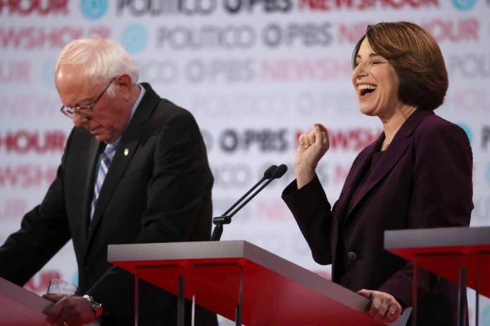 LOS ANGELES, CALIFORNIA - DECEMBER 19: Democratic presidential candidatte Sen. Amy Klobuchar (D-MN) speaks as Sen. Bernie Sanders (I-VT) listens during the Democratic presidential primary debate at Loyola Marymount University on December 19, 2019 in Los Angeles, California. Seven candidates out of the crowded field qualified for the 6th and last Democratic presidential primary debate of 2019 hosted by PBS NewsHour and Politico. (Photo by Justin Sullivan/Getty Images)