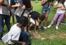 "Rising third-graders attending Denver Public Schools' ""summer academy"" stop to inspect a mushroom during a nature walk. (Photo by Melanie Asmar, Chalkbeat)"