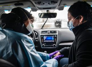 """Nurse Practitioner Lisa Robbiano, left, talks to Fabiola Grajales, 27, while checking her lungs and heart rate in Robbiano's car next to the MIRA COVID-19 testing bus in El Jebel on Thursday, April 16, 2020. This was Grajales's fourth COVID-19 test. She was confirmed positive during the three prior tests and was positive for pneumonia. She first got sick on March 2nd with flu-like symptoms and had been on three different antibiotics since. """"I can't imagine how it is for people who don't have insurance, who don't speak the language, and who don't have any knowledge of how the medical system works,"""" said Grajales about her experience with COVID-19 testing."""