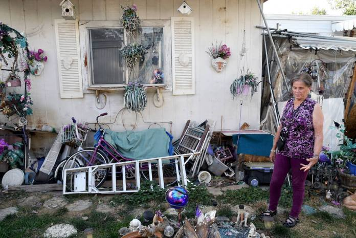 Doretta Hultquist looks at decorations in her yard at the San Souci Mobile Home Park south of Boulder, Colo., on Saturday, Aug. 31, 2019. Residents say that after Colorado-based RV Horizons bought the property in 2018, rents were raised, the company started charging residents for well water and strict rules were put in place governing anything from lawn care to what kind of curtains can be hung. (AP Photo/Thomas Peipert)
